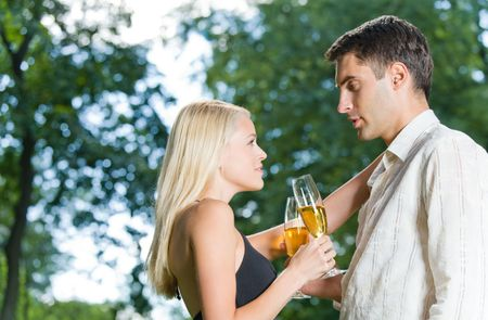 Evening portrait of young happy couple celebrating outdoors photo