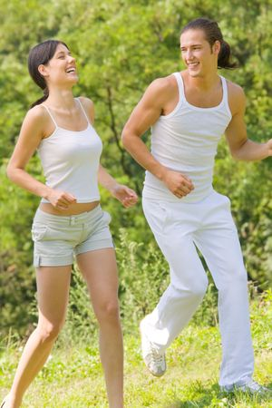 Young attractive happy couple running together outdoors photo