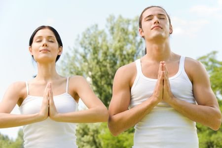 Young couple doing yoga moves or meditating together outdoors  photo