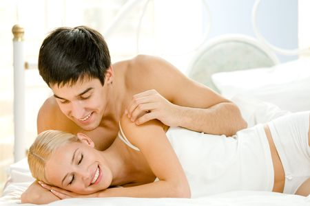 Young attractive happy amorous couple at bedroom Stock Photo - 3413520