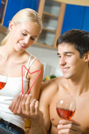 Couple celebrating with red wine and self-made heart symbol made by combination of two cocktail tubules, at home photo