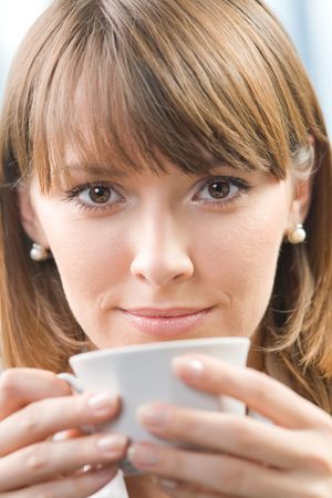 Portrait of young happy smiling businesswoman with coffee at office photo
