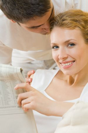 Young amorous couple reading newspaper at home photo