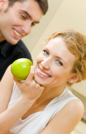 amorous: Portrait of young amorous couple with apple at home Stock Photo