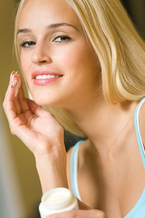 humidify: Young happy smiling woman with cosmetic cream at home Stock Photo