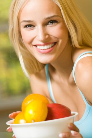 Portrait of young happy smiling woman with plate of fruits Stock Photo - 3632388