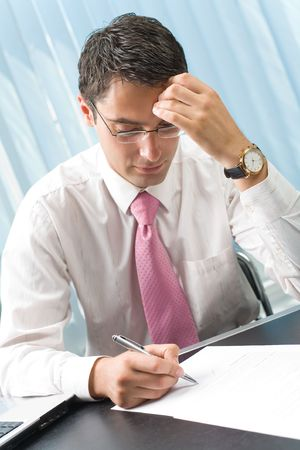 reflecting: Photo of thinking businessman with pen at office