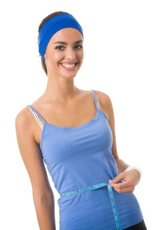 Woman in sportswear measuring waist with a tape measure, isolated Stock Photo