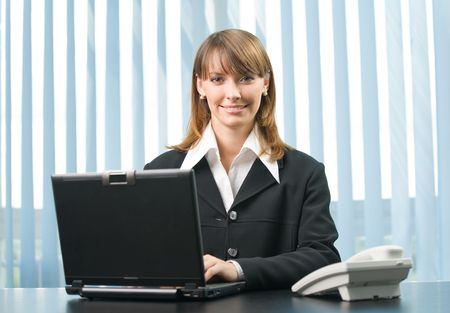 secretary office: Happy businesswoman working with laptop at office