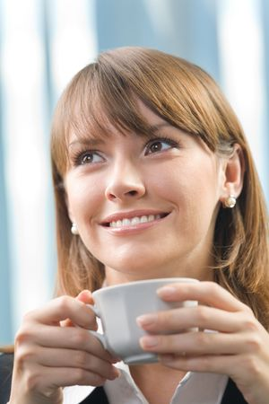 Happy businesswoman with a cup of coffee or tea at office photo