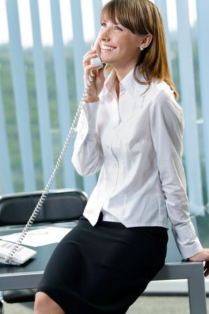 Portrait of happy smiling businesswoman on phone at office photo