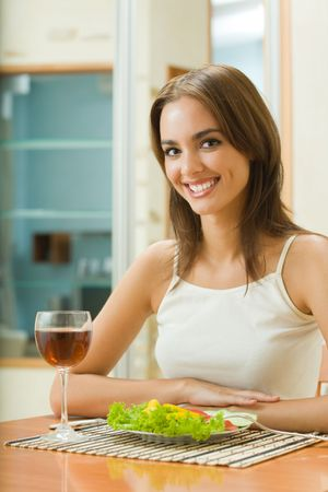 Young woman with glass of redwine and salad at home Stock Photo - 3662919