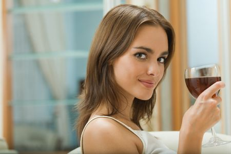 Portrait of young woman with glass of red wine at home Stock Photo - 3662908
