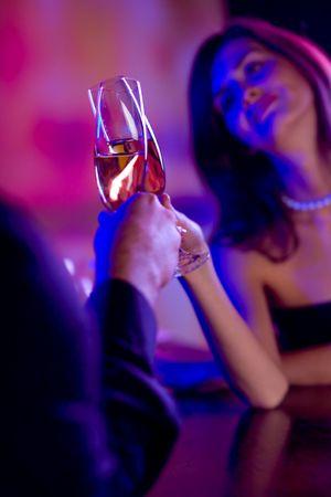 jovenes tomando alcohol: Joven pareja feliz con champ�n en vasos de celebraci�n. Centrarse en las gafas.
