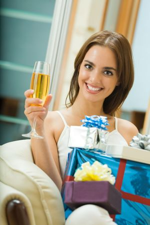Young happy smiling woman with gifts and champagne at home photo