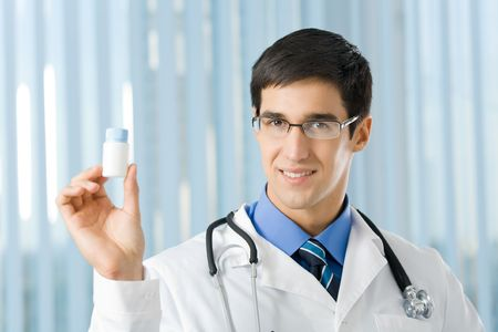 Happy doctor with drug at office photo