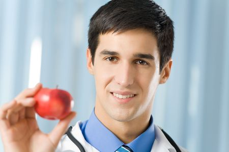 Happy doctor with apple at office Stock Photo - 3760094