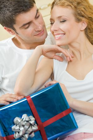 Young happy amorous couple with gift at home photo