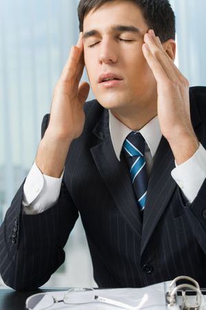 Photo of tired or unhealthy businessman at workplace photo