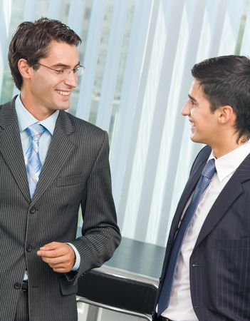 25 30: Two happy successful businessmen talking at office