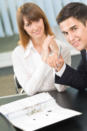 25 30: Two businesspeople working together at office