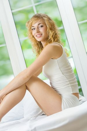 Young happy smiling attractive woman in lingerie at bedroom Stock Photo - 3900848