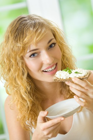 crispbread: Woman eating crispbread with cheese and parsley at home Stock Photo