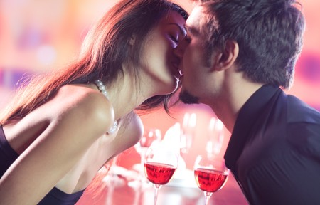 Couple kissing on romantic date or celebrating together at restaurant photo