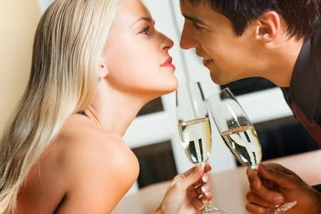 flirt: Couple kissing on romantic date or celebrating together at restaurant