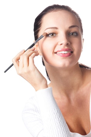 20 25: Young smiling woman applying eye shadow, isolated on white