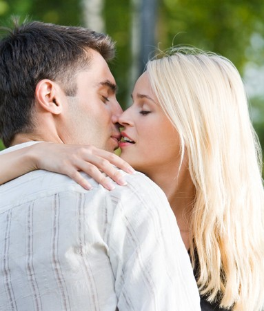 Young happy amorous couple kissing, outdoors Stock Photo - 4331160