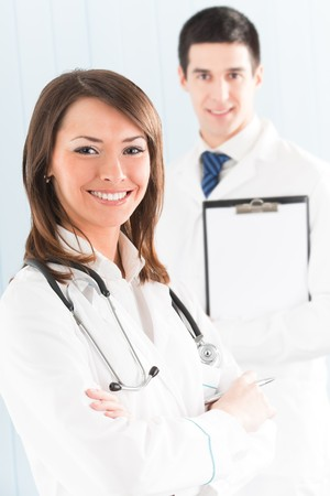 Portrait of two happy smiling medical people at office. Focus on woman. photo