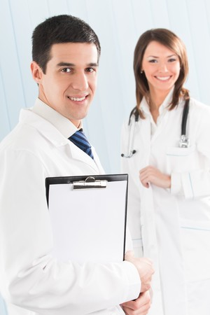Portrait of two happy smiling medical people at office. Focus on man. photo
