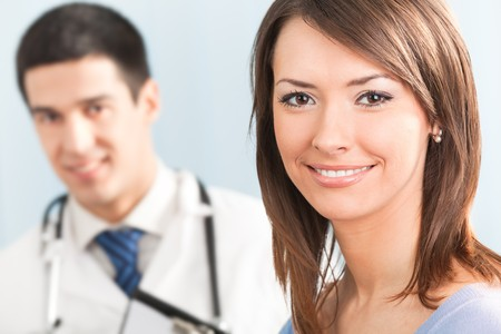 Portrait of happy smiling patient and doctor on backgroud. Focus on woman. photo