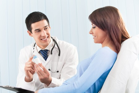 Happy doctor with drug and patient on bed at clinic Stock Photo - 4408221