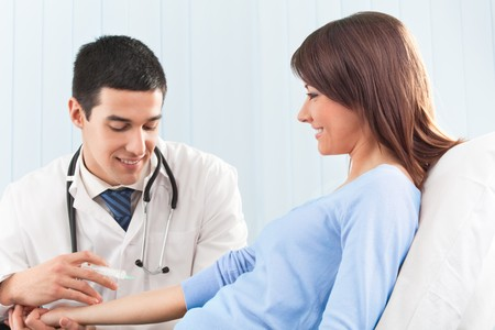 Happy doctor giving an injection to female patient Stock Photo - 4408245