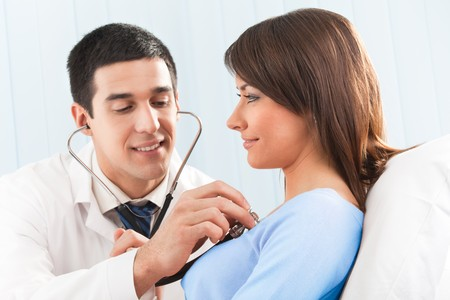 Doctor with stethoscope and female patient on bed at clinic Stock Photo - 4408122