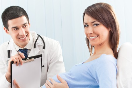 Doctor and pregnant female patient on bed at clinic photo