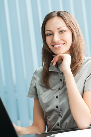 Happy businesswoman working with laptop at office Stock Photo - 4444229