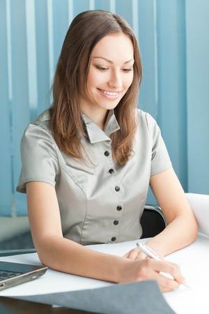Happy businesswoman signing document at office Stock Photo - 4444230