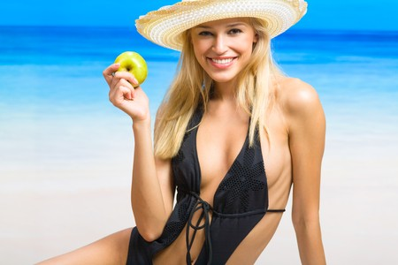Young beautiful smiling woman with apple on sea beach  photo