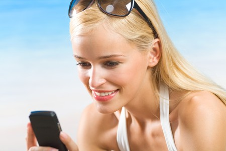 mobilephones: Young beautiful woman with cellphone on beach