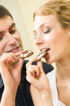 Young amorous couple eating cookies together at home Stock Photo - 4444221