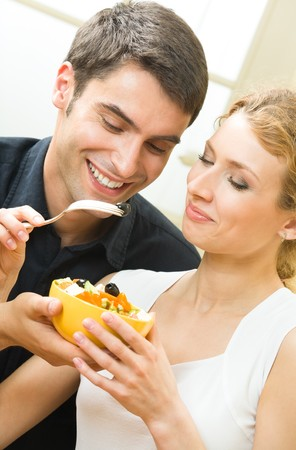 Young amorous couple eating vegetable salad together at home photo