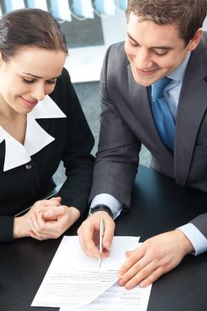 Two happy businesspeople signing document at office photo