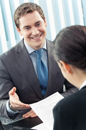 Two businesspeople, or businessman and client, with document at office Stock Photo