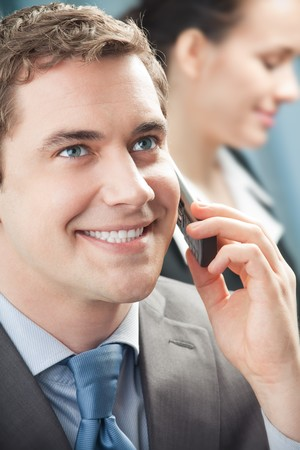 Businessman with cellphone and colleague on background, at office Stock Photo - 4492749
