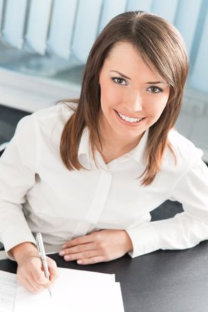 Happy businesswoman signing document at office photo
