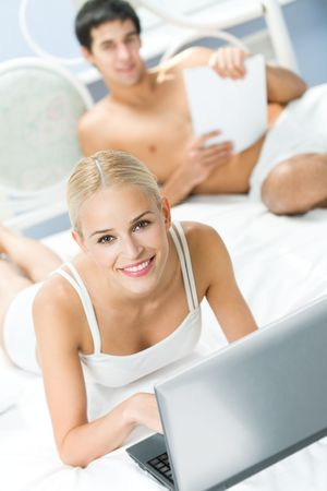 Young happy couple with laptop at bedroom Stock Photo - 4702310