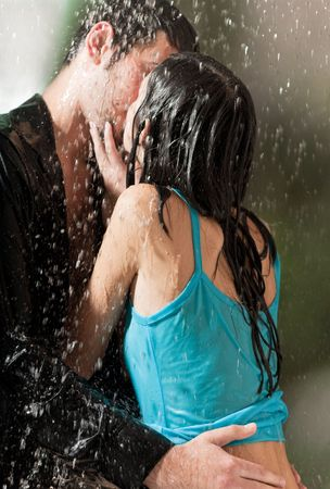 Young happy couple hugging under a rain photo
